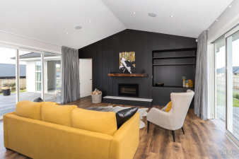 4 – An inky black feature wall adds a dramatic touch to the light-filled living room in this Waiata showhome, by Landmark Homes. Image: 4